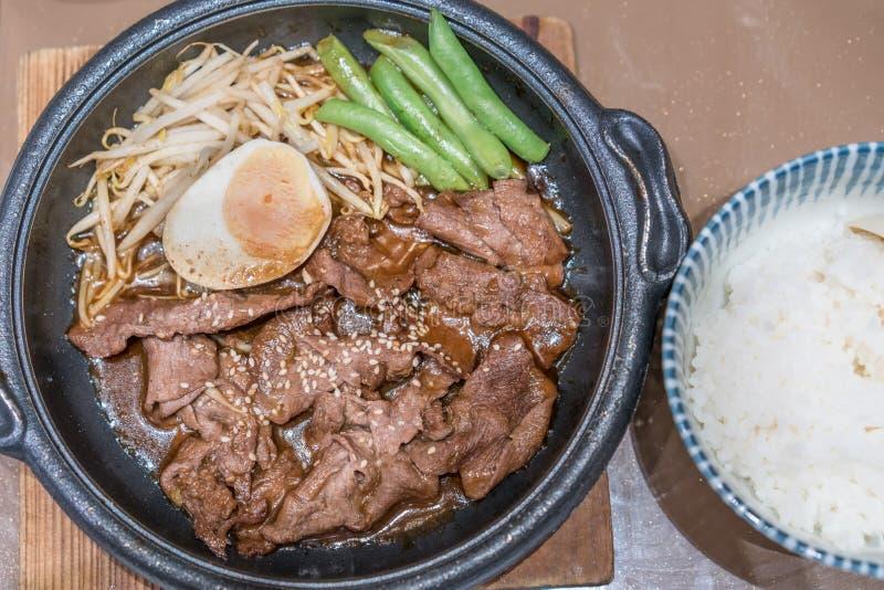 Korean grillade griskött i varm panna med ägget, grodden och ärtor på si royaltyfri foto