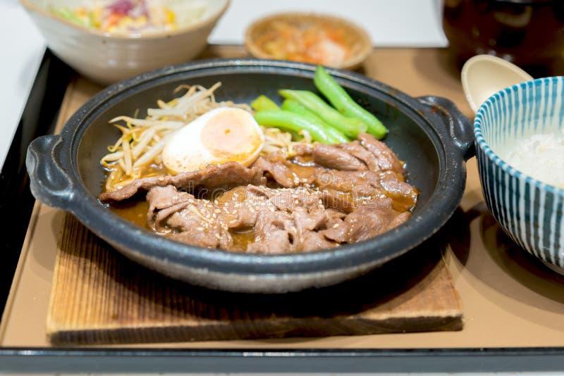 Korean grillade griskött i varm panna med ägget, grodden och ärtor på si fotografering för bildbyråer