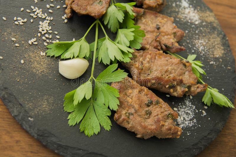 Korean grilled meat, bulgogi. Barbecue meat slices closeup. Korean grilled meat, bulgogi. Barbecue meat slices with scattered spices, sesame on dark slate stock image