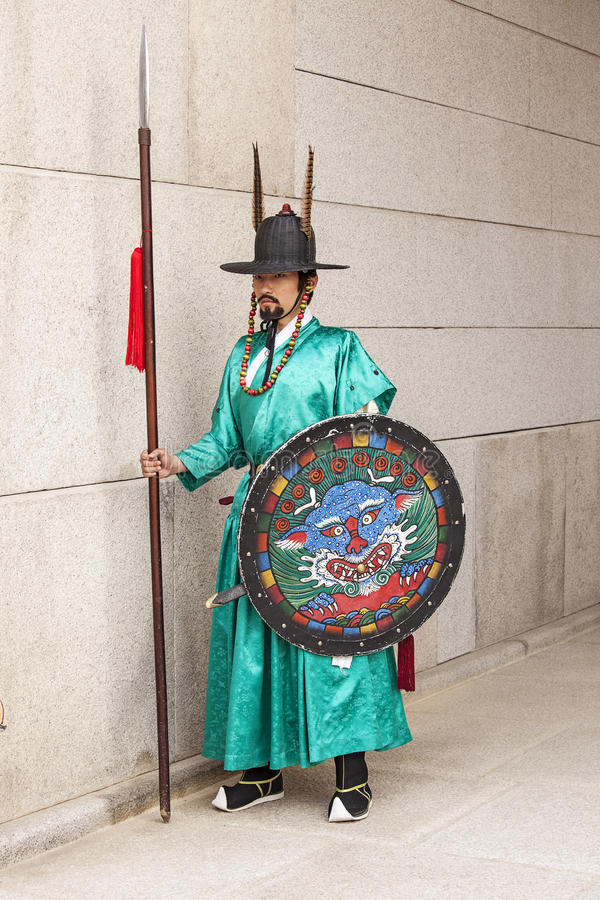 Korean Guard In Teal Uniform. SEOUL, KOREA - APRIL 27, 2012: A guard in a teal green uniform stands at attention at the entrance to the Gyeongbokgung Palace stock images