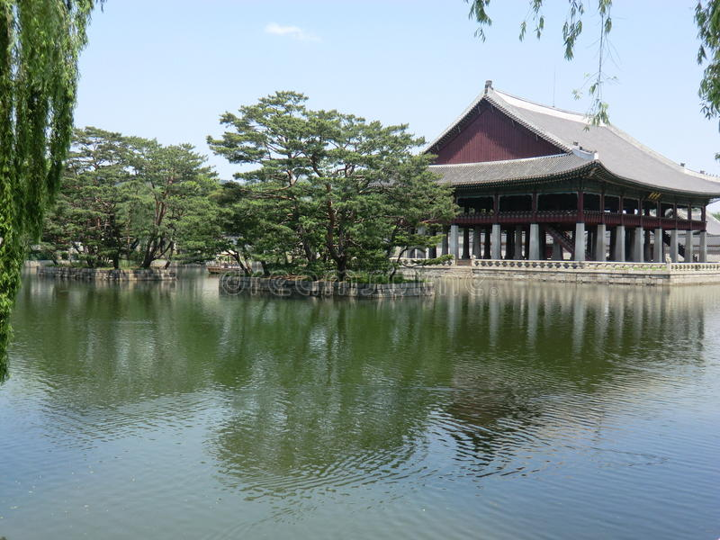 A Korean Lake And Palace in Seoul, South Korea. A Korean lake with stone walled islands and trees. In the background, a large wooden Palace building. In the stock images