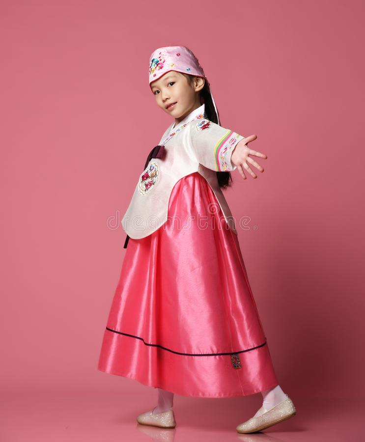 Korean little baby girl in traditional silk dress for new year celebration dancing on pink with hands spread royalty free stock images
