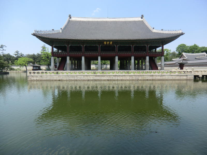 Korean Palace On The Edge Of A Lake. A Korean Palace In Seoul. Surrounded by a stone balustrade on the edge of a calm water lake with fish. A clear blue sky with royalty free stock images