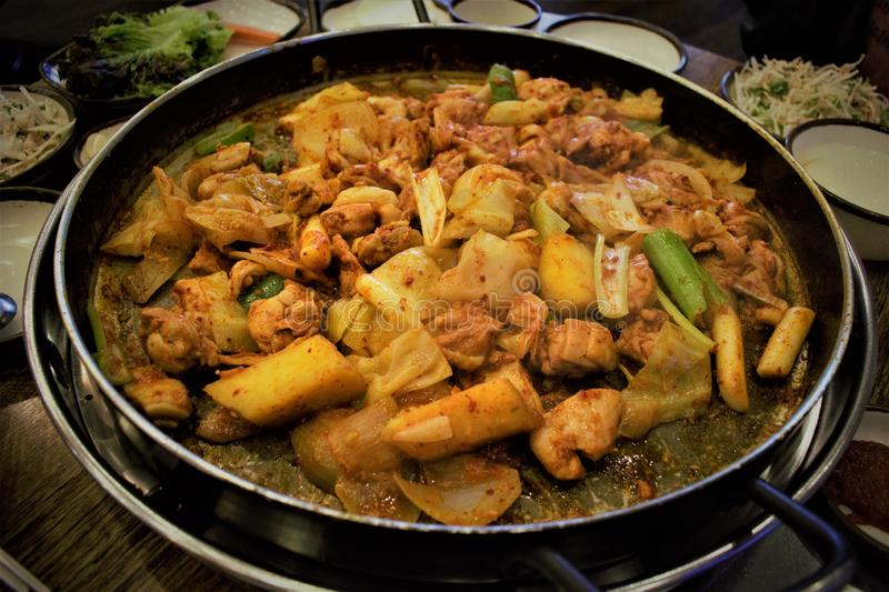 Korean spicy stir-fried chicken Dak-galbi. With potaoes, onions and rice cakes stock photography