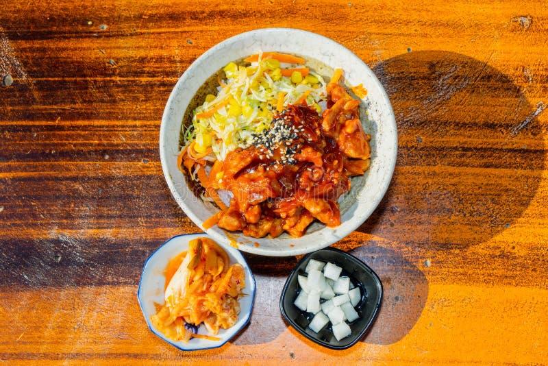 Korean stir fried chicken rice in white bowl on wooden table stock photo