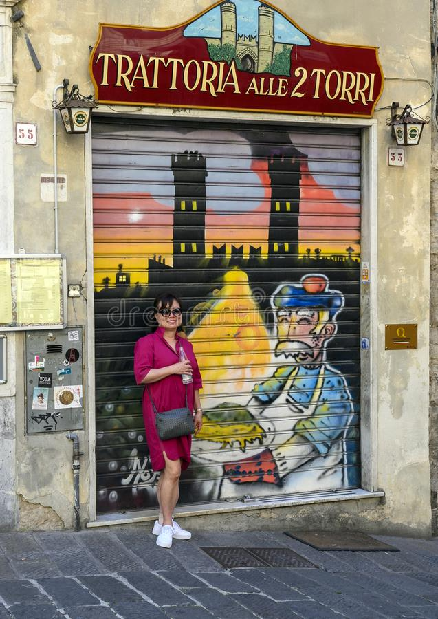 Korean tourist woman by colorful painted pull down protective door on restaruant on a street in Genoa, Italy royalty free stock image