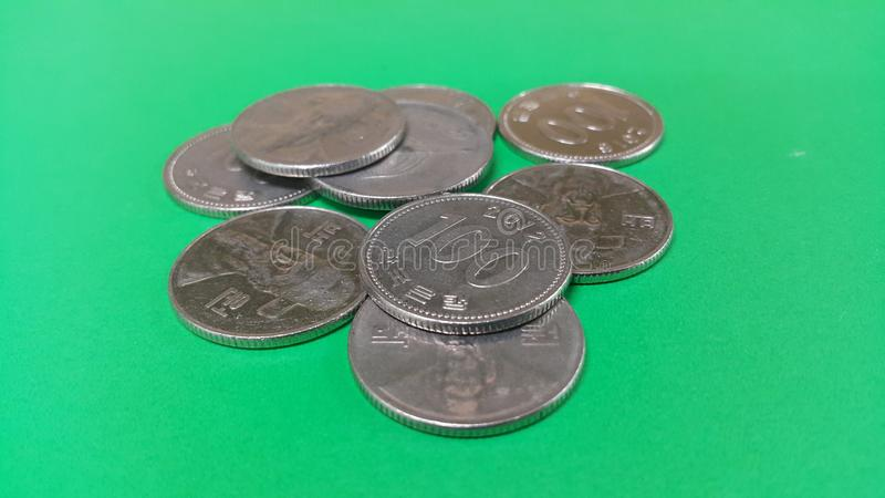 Korean won coin scattered over a green floor. Silver shining Korean won coin scattered over a green floor money cash finance currency metal economy investment royalty free stock photos