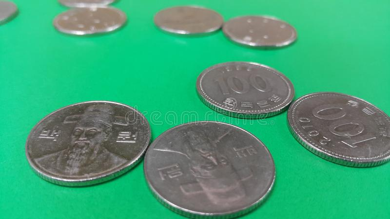 Korean won coin scattered over a green floor. Silver shining Korean won coin scattered over a green floor money cash finance currency metal economy investment stock photos