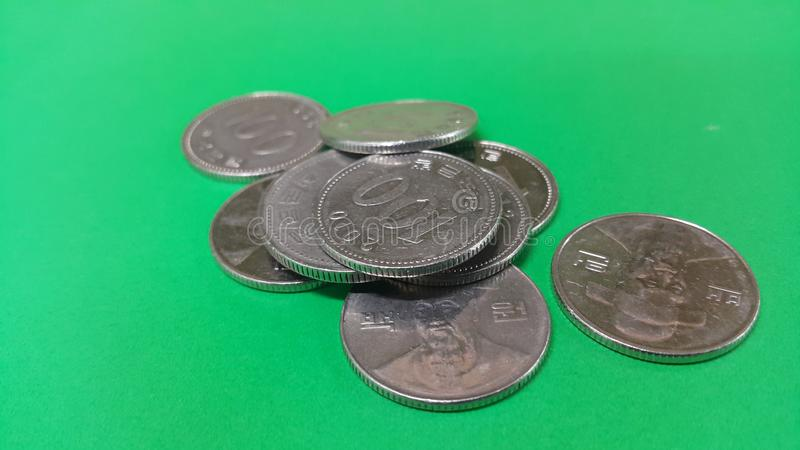 Korean won coin scattered over a green floor. Silver shining Korean won coin scattered over a green floor money cash finance currency metal economy investment royalty free stock images