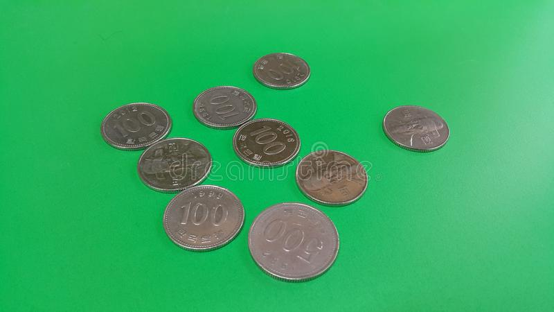 Korean won coin scattered over a green floor. Silver shining Korean won coin scattered over a green floor money cash finance currency metal economy investment royalty free stock image