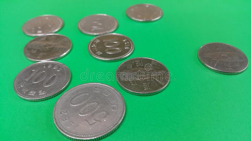 Korean won coin scattered over a green floor. Silver shining Korean won coin scattered over a green floor money cash finance currency metal economy investment royalty free stock photography