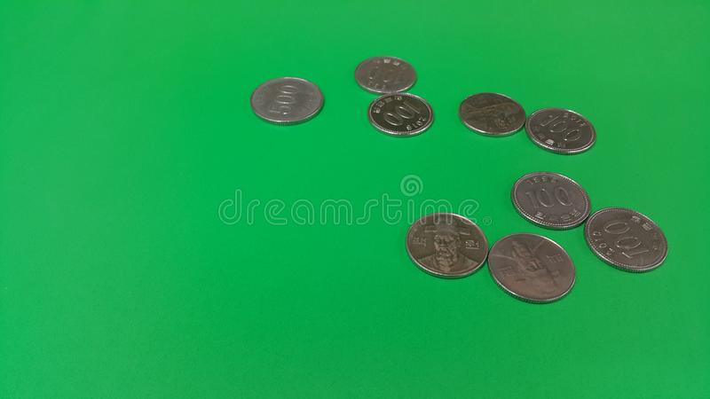 Korean won coin scattered over a green floor. Silver shining Korean won coin scattered over a green floor money cash finance currency metal economy investment royalty free stock photo