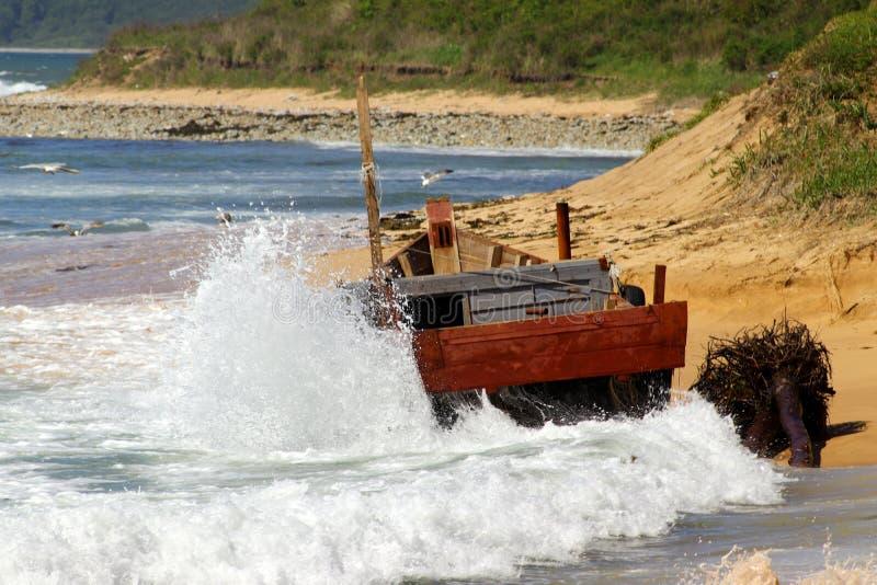 Korean wooden fishing boat wrecking on sandy beach. Big storm waves hitting the boat. Drama of poor north korean fishermen. stock photo