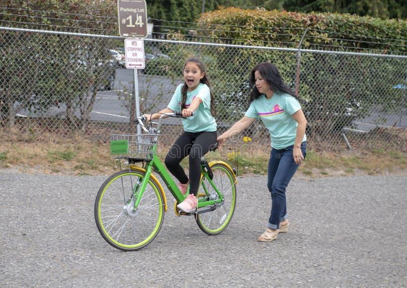 Koreanische Mutter hilft ihrer zehn Jährige Amerasian-Tochterfahrt ein Fahrrad in Seattle, Washington stockfoto