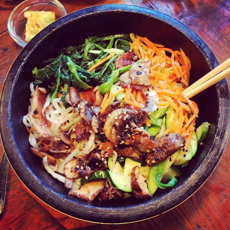 Koreansk kokkonst med grönsaker och pinnar i en svart bunke royaltyfri foto