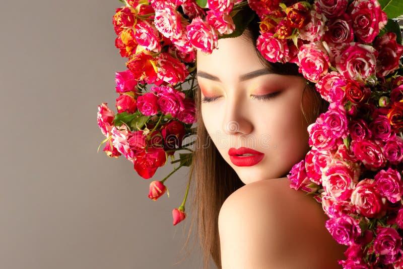 Koreansk kvinna med ljus makeup och rosor på huvudcloseupen arkivfoto