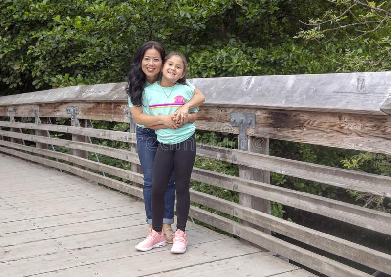 Koreansk moder som poserar affectionately med hennes dotter på en träbro i Washington Park Arboretum, Seattle, Washington royaltyfri fotografi