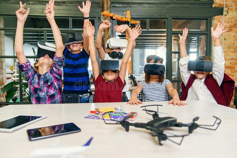 Koreanska forskare med gruppen unga elever med headset på bärbara datorer och VR under en datorklass Utslagen royaltyfri fotografi