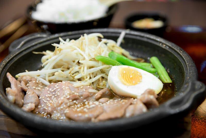 Koreanskt kryddigt bbq-griskött tjänade som på en varm platta med sidodisk royaltyfri bild