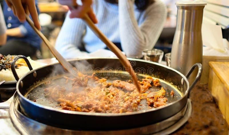 Koreanskt kryddigt Kimchi bbq-griskött tjänade som på en varm panna med sidodisk och ris som en bakgrund royaltyfri foto