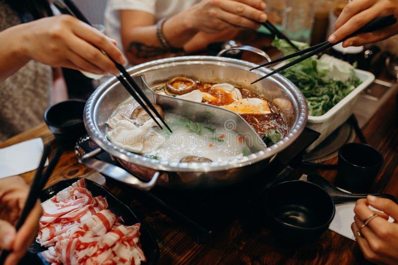 Koreanskt varmt krukamål Händer som tar mat med pinnar arkivfoto