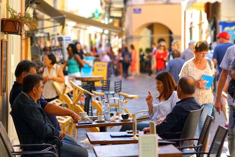 KORFU, GRIEKENLAND, 18 2018, mensen ontspant bij de bar het drinken koffie stock fotografie