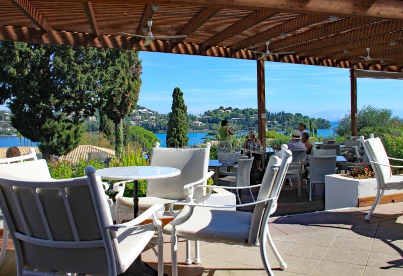 KORFU, GRIEKENLAND - OKTOBER VIJFDE 2012: Behandeld bargebied van vakantiehotel met prachtige mening over het nabijgelegen overze stock foto