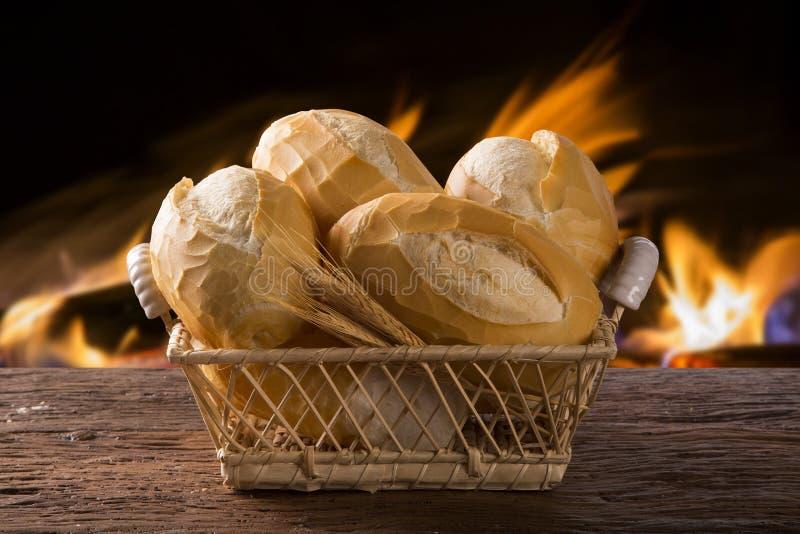 Korg av `-franskbröd`, traditionellt brasilianskt bröd med brandbakgrund arkivbilder