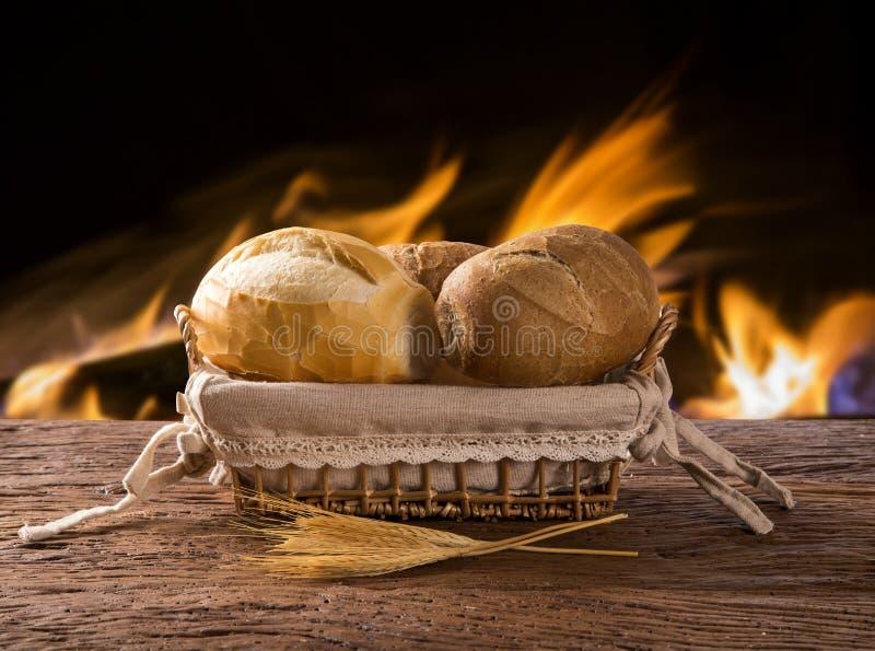 Korg av `-franskbröd`, traditionellt brasilianskt bröd med brandbakgrund arkivfoton