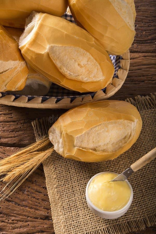Korg av `-franskbröd`, traditionellt brasilianskt bröd med smör på wood bakgrund arkivfoton