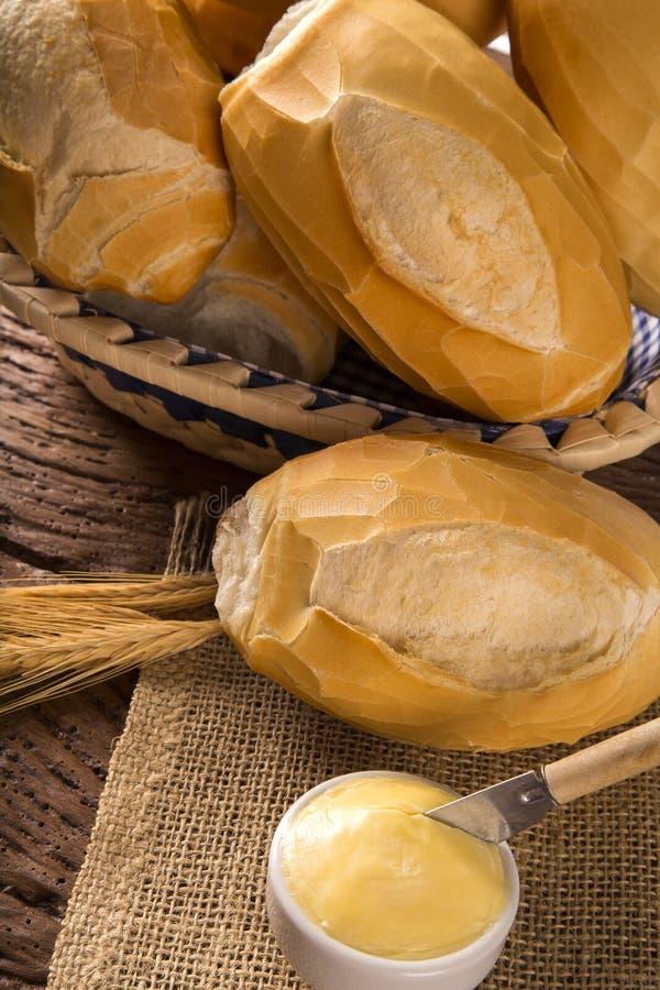 Korg av `-franskbröd`, traditionellt brasilianskt bröd med smör på wood bakgrund royaltyfri fotografi