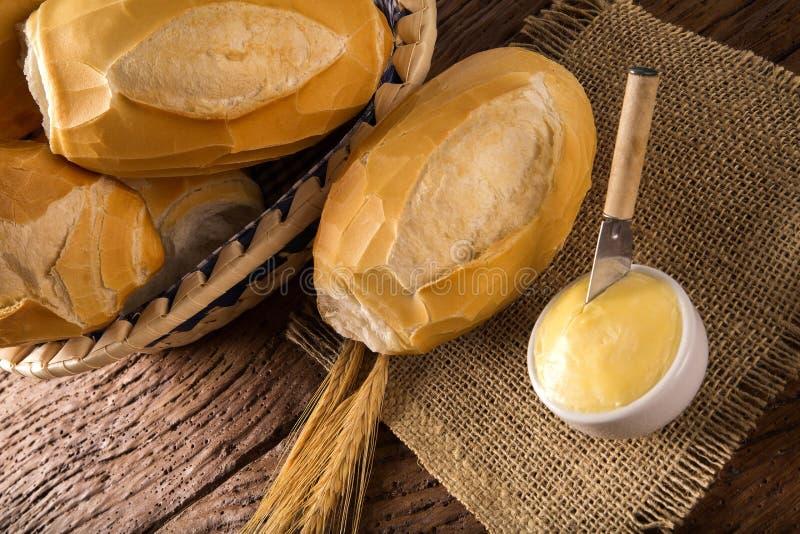 Korg av `-franskbröd`, traditionellt brasilianskt bröd med smör på wood bakgrund royaltyfri foto