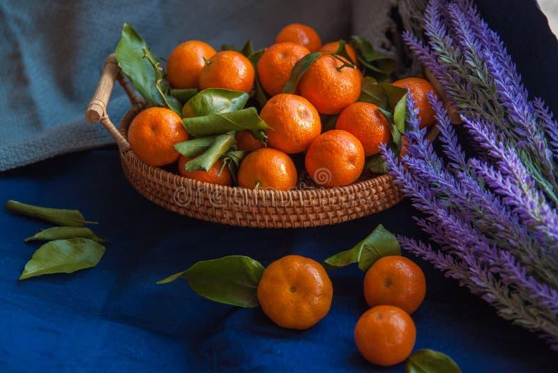 Korg av nya mandariner Tangerins med gröna sidor arkivfoton