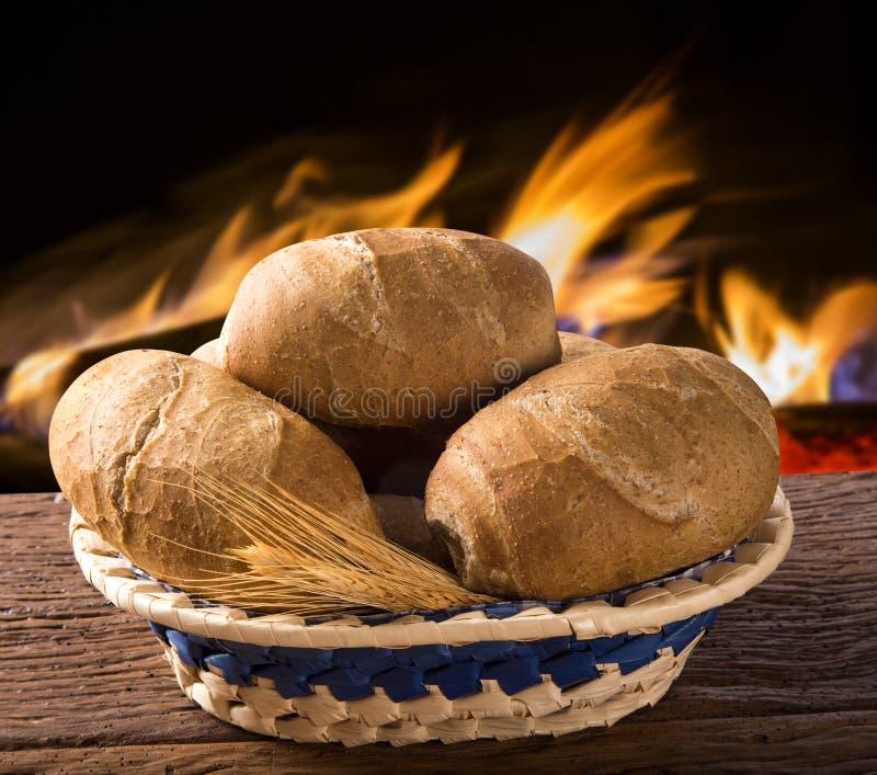 Korg av väsentlig franskbröd` för `, traditionellt brasilianskt bröd med brandbakgrund royaltyfri foto