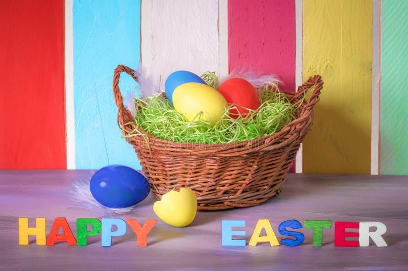Korg med ägg och lyckliga easter ord royaltyfri foto