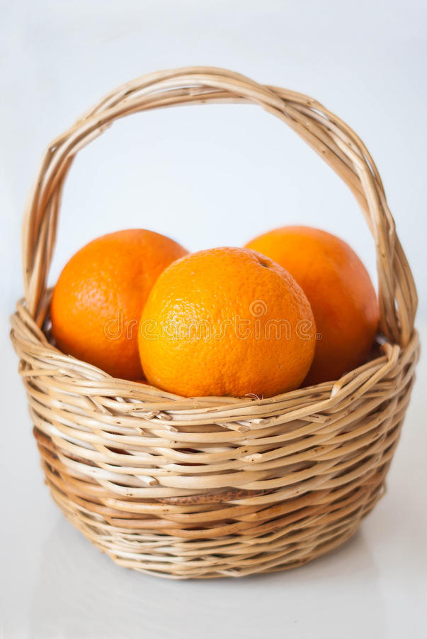 Korg med de nya saftiga apelsinerna, på den vita tabellen, reflecti arkivbild