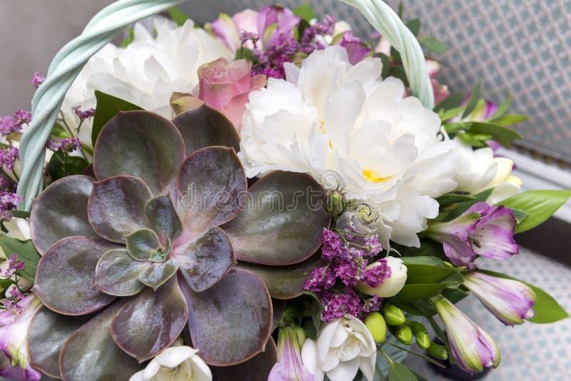 Korg med en bukett av blommor med succulenta, vita pioner och rosa rosor arkivbilder