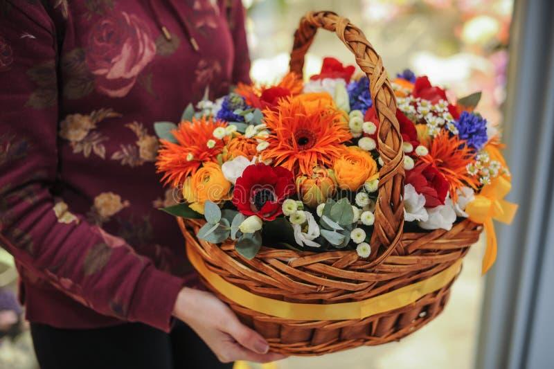 Korg med en bukett av färgrika blommor royaltyfri foto