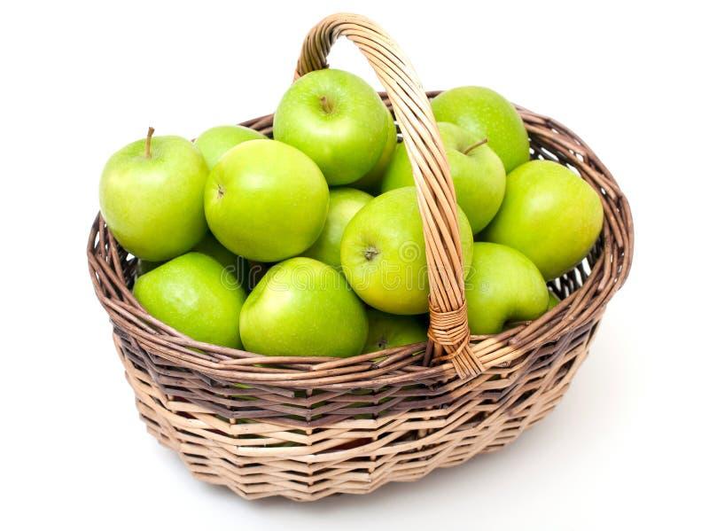 Korg med gröna äpplen arkivbilder