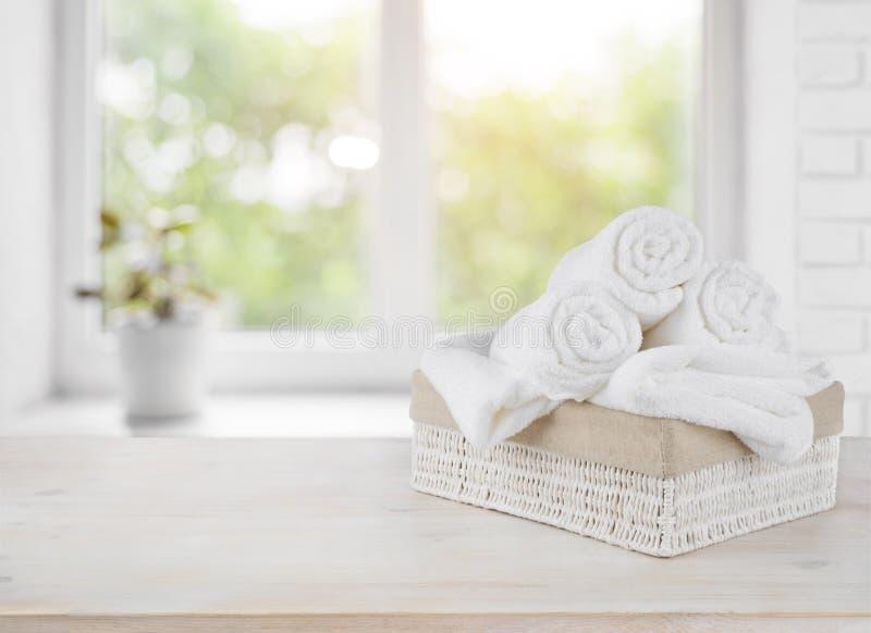 Korg med handdukar på fönsterfönsterbräda över bakgrund för sommardag fotografering för bildbyråer