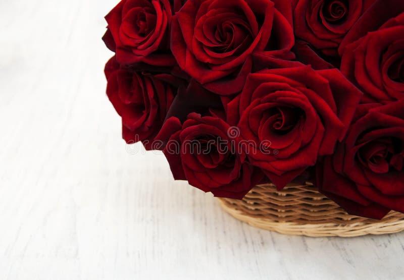 Korg med nya röda rosor arkivbilder