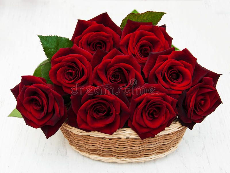 Korg med nya röda rosor arkivfoton