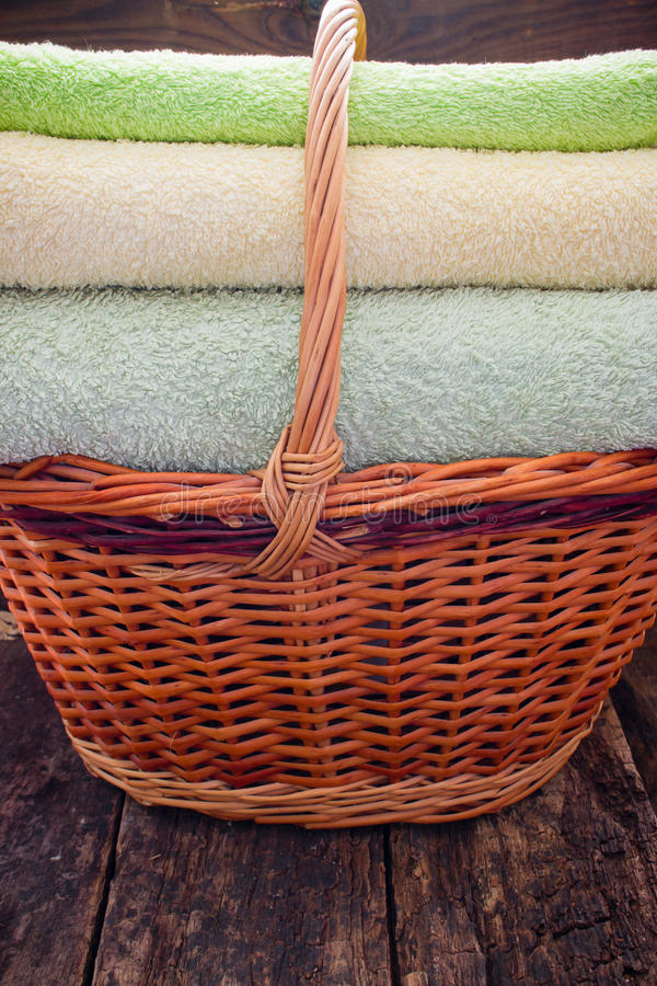 Korg med nya rena färgrika handdukar på ett trä arkivfoton