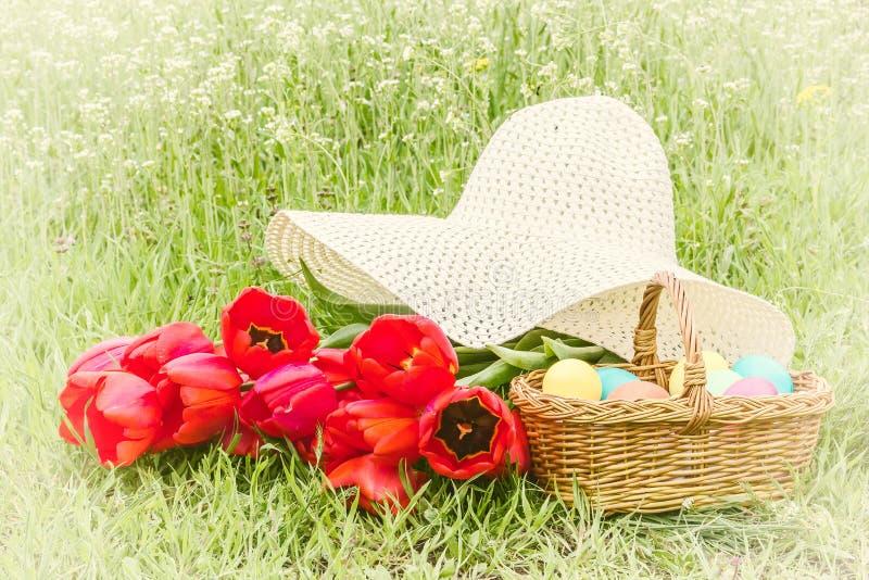 Korg med påskägg, röda tulpan, hatt royaltyfri foto