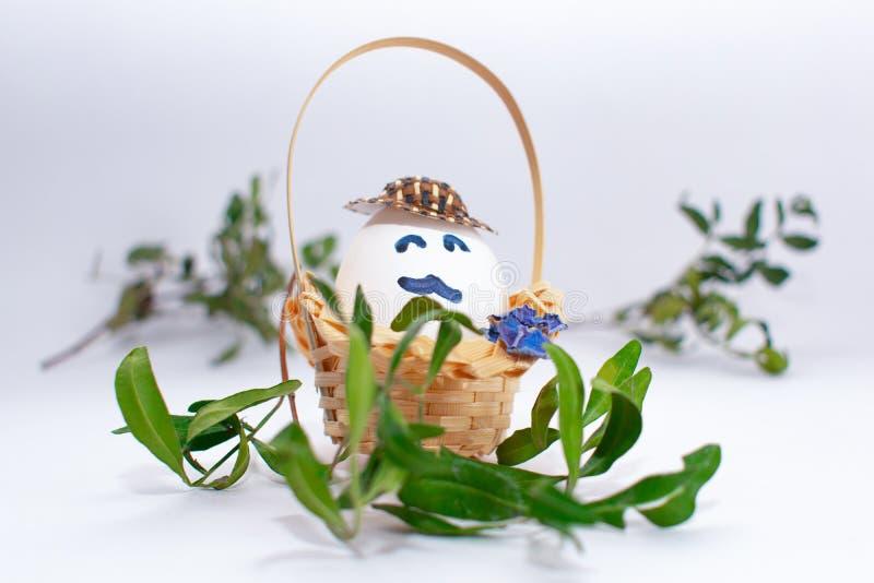 Korg med påskägget med en mustasch i en filial för hatt och för grönt gräs på vit pastellfärgad bakgrund idérik idé Konstmatbegre arkivfoton