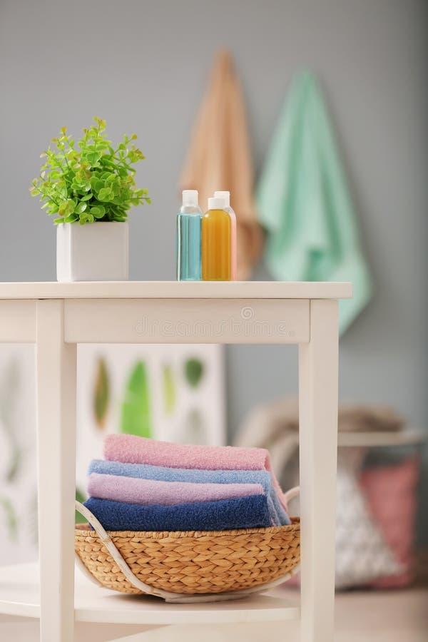 Korg med rena handdukar och skönhetsmedel på hyllor fotografering för bildbyråer