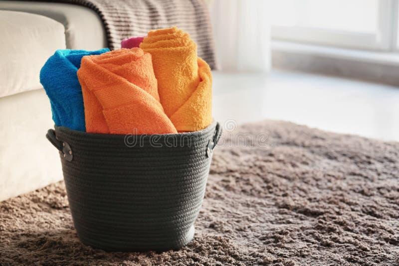 Korg med rullande rena handdukar på golv i rum arkivfoto