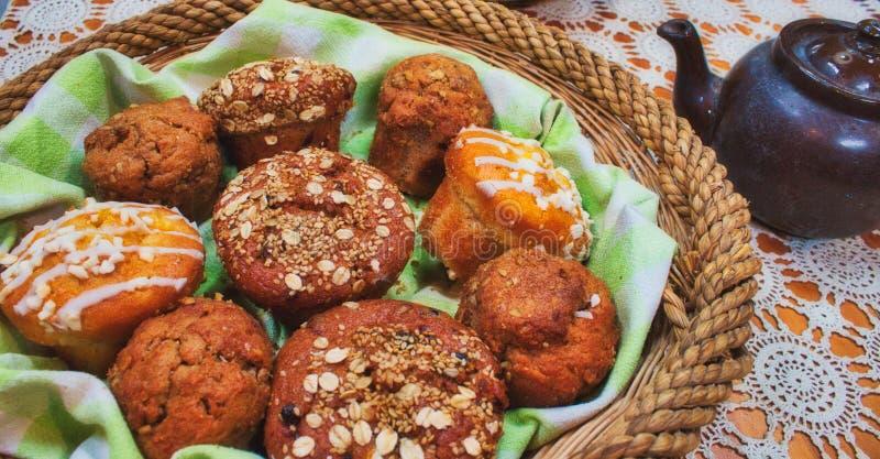 Korg mycket av nytt bakade muffin på en tabell med en tekanna royaltyfri fotografi