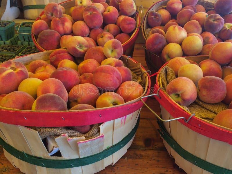 Korgar av nya persikor arkivfoto