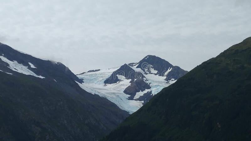 Korkad bergöverkant för snö under en tungt fördunklad himmel arkivfoto